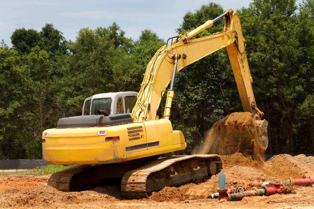 an excavator cutting out a section of dirt and filling in a low area of the work site