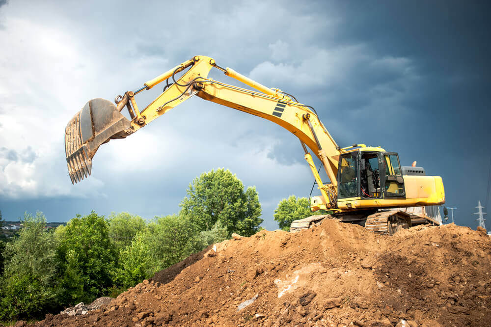 a yellow excavator reaching out its arm to get some dirt from the lower area of the mound that it sits on